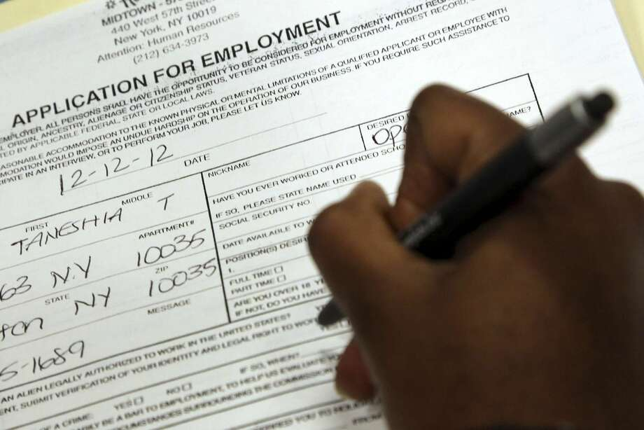 In this Wednesday, Dec. 12, 2012 photo, Taneshia Wright, of Manhattan, fills out a job application during a job fair in New York. (AP Photo/Mary Altaffer)