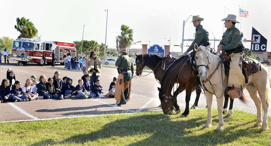 United Day School students listen to Border Patrol agents, who sometimes use horses to navigate rough terrain, at their Career Day Friday morning. Students were visited by law enforcement, fire department officials and other professionals. (Photo by Cuate Santos/Laredo Morning Times)