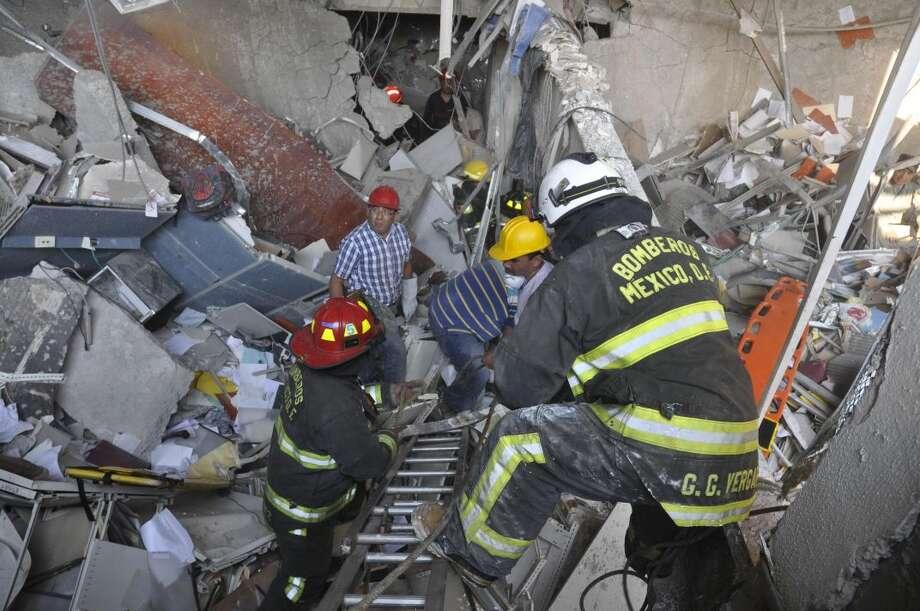 Bomberos pertenecientes al sector Tacubaya y trabajadores buscan sobrevivientes después de una explosión en un edificio adyacente a la torre ejecutiva de Pemex, la compañía petrolera paraestatal, en la Ciudad de México, el jueves. (Foto AP/Guillermo Gutiérrez)