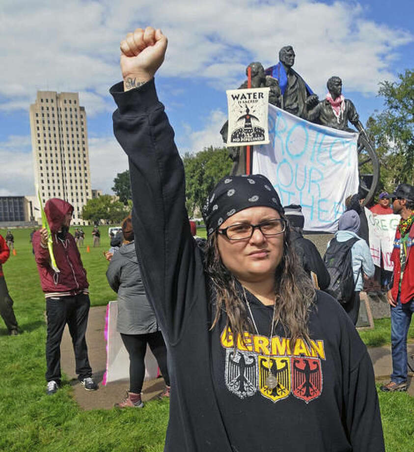 "Megan Tobin, of Bellevue, Ohio protests on the grounds of the North Dakota state capitol Friday, Sept. 9, 2016 in Bismarck, N.D. The federal government stepped into the fight over the Dakota Access oil pipeline Friday, ordering work to stop on one segment of the project in North Dakota and asking the Texas-based company building it to ""voluntarily pause"" action on a wider span that an American Indian tribe says holds sacred artifacts. (Tom Stromme/The Bismarck Tribune via AP)"