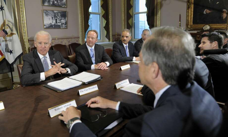 Vice President Joe Biden, left, with Attorney General Eric Holder, second from right, speaks during a meeting with representatives from the video game industry in the Eisenhower Executive Office Building on the White House complex in Washington, Friday, Jan. 11, 2013. (AP Photo/Susan Walsh)