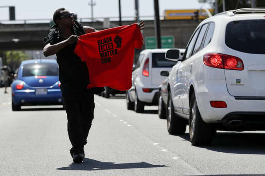 "A man waves a shirt as he and others block a street during a protest Wednesday, Sept. 28, 2016, in El Cajon, Calif. Dozens of demonstrators on Wednesday protested the killing of a black man shot by an officer after authorities said the man pulled an object from a pocket, pointed it and assumed a ""shooting stance."" (AP Photo/Gregory Bull)"