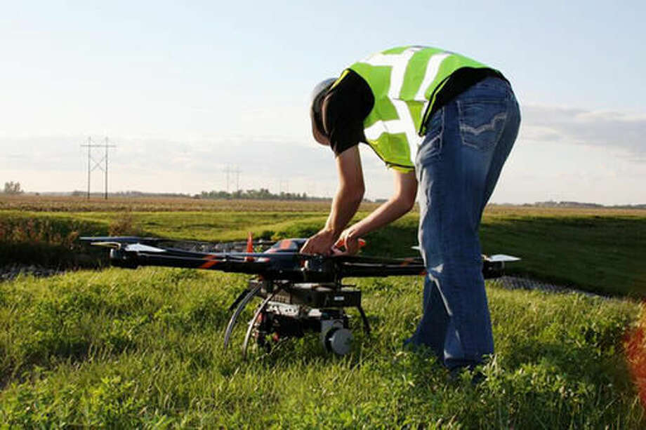 FILE - In this Aug. 29, 2016, file photo provided by Sharper Shape and SkySkopes, Cory Vinger, senior instructor pilot for SkySkopes, prepares a Sharper A6 drone for a test flight in eastern North Dakota near Blanchard. The Sharper Shape drone is being used in pilot project to see if drones can help crews respond more quickly to natural disasters. It is specially designed for utility asset inspections. (Sharper Shape and SkySkopes via AP)