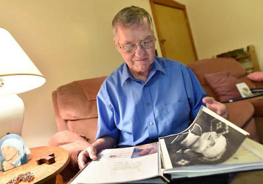 "In this Aug. 23, 2016 photo, Paul Ahearn turns the pages of a scrapbook filled with artifacts and correspondence with Mother Teresa, at his home in Streator, Ill. Not too many people can say they had a letter correspondence with a saint, but Ahearn can. Beginning in 1985, he, and Mother Teresa exchanged letters, until a few months before she died. Dubbed the ""Saint of the Slums"" for her work with the poorest of the poor Mother Teresa was canonized by Pope Francis, Sept. 4 2016. (Doug Larson/Ottawa Times via AP)"