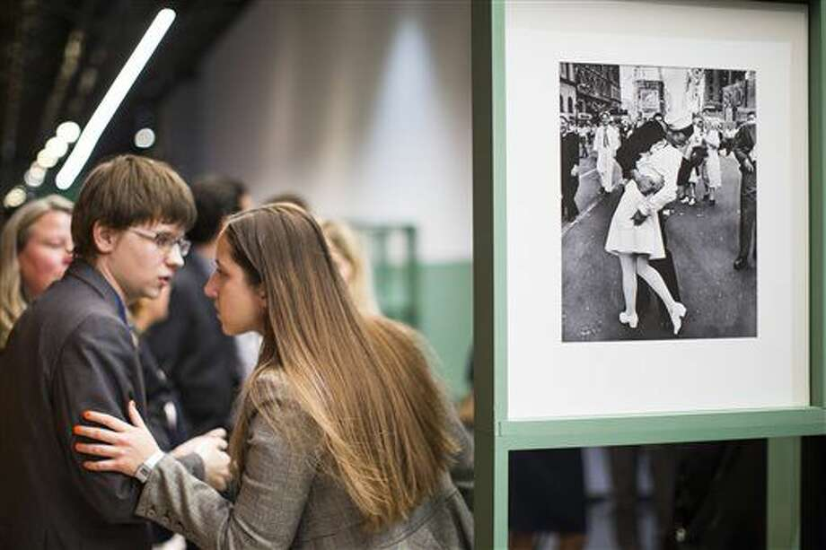 """FILE - In this April 14, 2015 file photo, people speak next to a famous photograph taken by Alfred Eisenstaedt of a sailor kissing a nurse in New York's Times Square on V-J Day, right, as they visit the exhibition of German-American """"Life"""" magazine photographer Alfred Eisenstaedt at Moscow's Jewish Museum and Tolerance Center in Moscow, Russia. The woman who was kissed by an ecstatic sailor in Times Square celebrating the end of World War II has died at the age of 92. Greta Zimmer Friedman's son says his mother died Thursday, sept. 8, 2016, at a hospital in Richmond, Virginia. She died from complications of old age, he said. (AP Photo/Alexander Zemlianichenko, File)"""