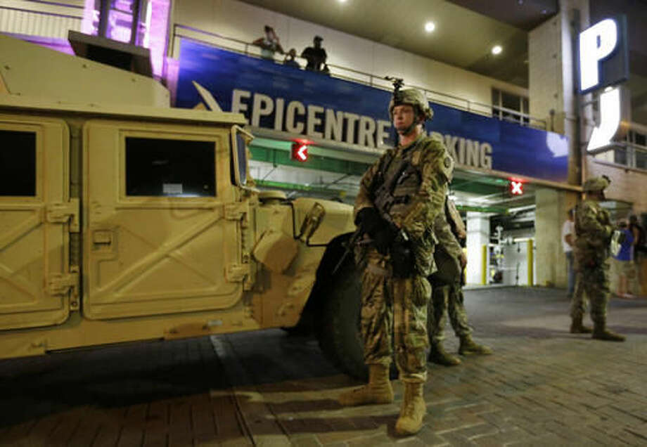 National Guardsman stand on the street in downtown Charlotte, N.C. on Thursday, Sept. 22, 2016. Charlotte police refused under mounting pressure Thursday to release video that could resolve wildly different accounts of the shooting of a black man, as the National Guard arrived to try to head off a third night of violence in this city on edge. (AP Photo/Chuck Burton)