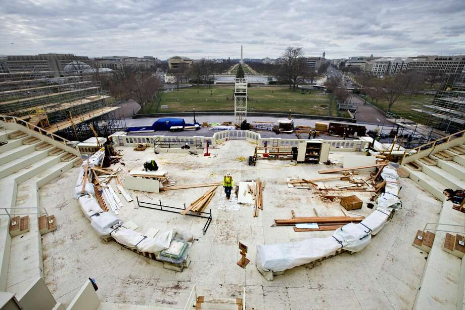 In this Dec. 11, 2012 file photo, construction workers continue work on the platforms on the west side of the Capitol where dignitaries and news cameras will witness the inaugural ceremonies on Capitol Hill in Washington. The pomp surrounding the inauguration of the president can carry a hefty price tag, from the glitzy galas to all those inaugural balls. Think of it this way: It can cost about the same as 150 luxury Bentley cars, several dozen yachts or some $20 million shy of the cash needed for a Boeing 737 passenger jet. But taxpayers aren't on the hook for the fun stuff _ the celebratory events like the balls. And this inauguration won't be as big as the last one for President Barack Obama. (AP Photo/J. Scott Applewhite, File)