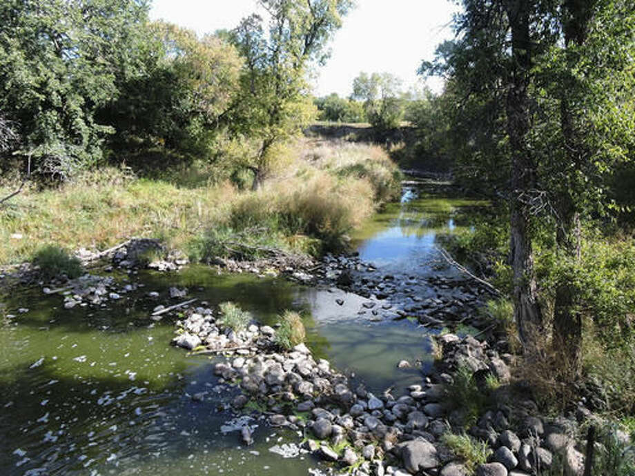 In this Sept. 16, 2016, photo, a view showing the Des Lacs River is seen at Old Settler's Park near Burlington, N.D. State health and wildlife officials are investigating a fish kill in the river in northern North Dakota. A lack of oxygen in the water due to low river levels this summer might have caused the fish kill, according to Jason Lee, a district fisheries supervisor with the state Game and Fish Department. (Kim Fundingsland/Minot Daily News via AP)