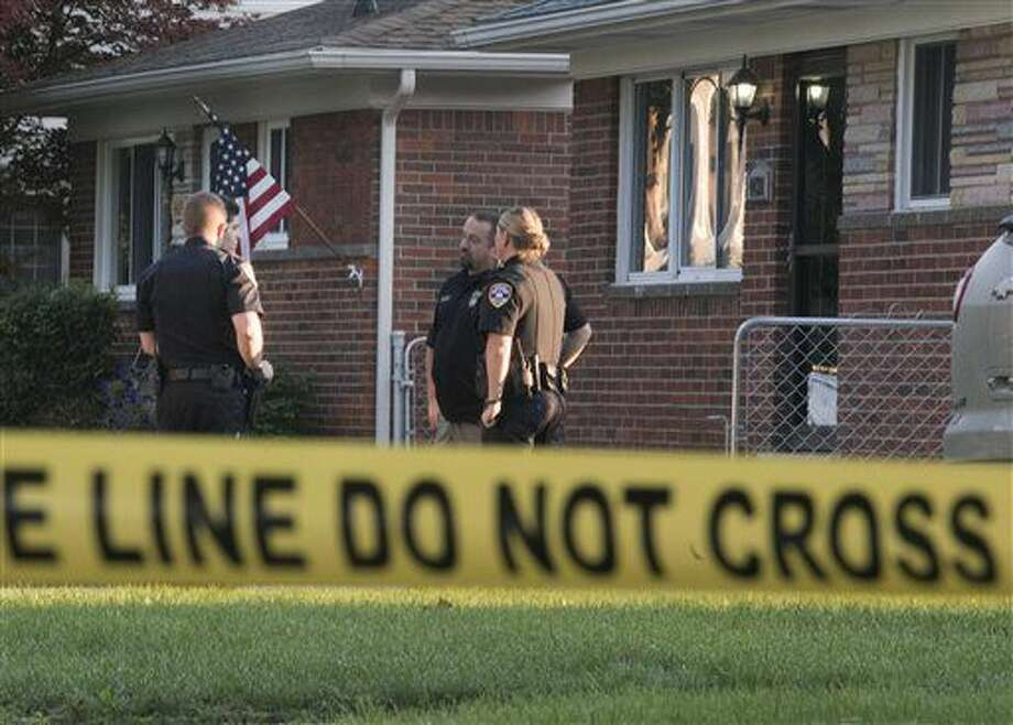 Dearborn Heights police stand outside a house at 431 Hipp street, in Dearborn Heights, Mich., on Wednesday, Sept. 21, 2016. A man is in custody after his two children were asphyxiated, his wife's two older children were fatally shot and his wife was shot and slashed at their suburban Detroit home, police said Wednesday. (Daniel Mears/The Detroit News via AP )