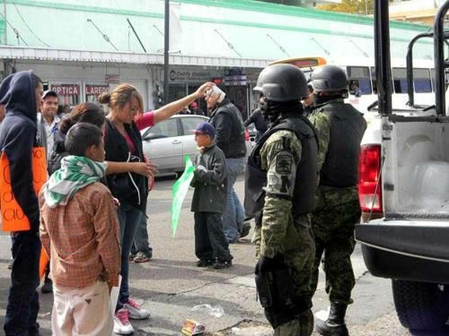 Foto de cortesíaUn promedio de 200 personas se apostaron en el crucero de avenida Guerrero y calle 15 de Junio, en Nuevo Laredo, México, el lunes por la mañana, exigiendo a militares abandonar la ciudad.