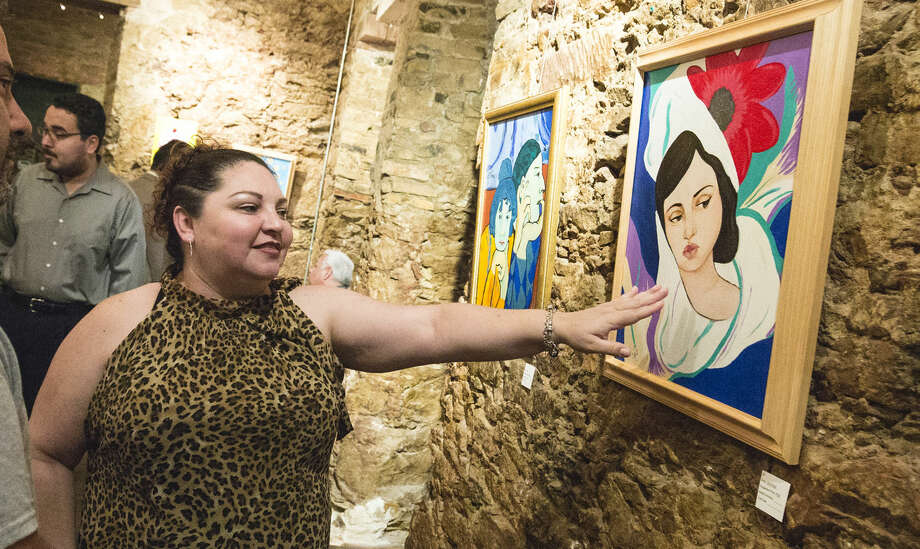 Cristina Arevalo showcases one of her paintings Oct. 10, 2015 during the Shira De Llano Art in Health Exhibit at Gallery 201.
