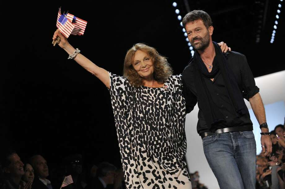 Designer Diane von Furstenberg waves American flags as she walks the runway with DVF creative director Yves Mispelaere, right, after the DVF Spring 2012 presentation during Fashion Week on Sunday, in New York. (AP Photo/Stephen Chernin)