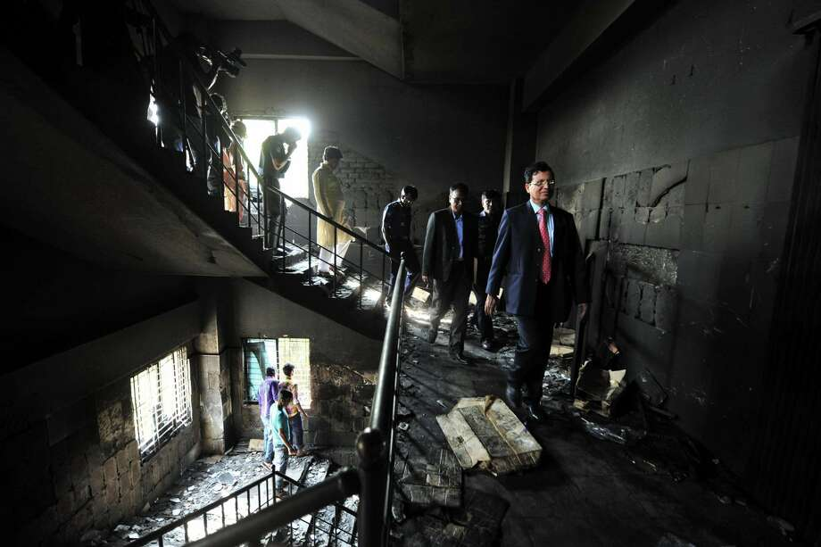 Bangladeshi officials inspect a garment-factory where a fire killed more than 110 people Saturday on the outskirts of Dhaka, Bangladesh, Monday, Nov. 26, 2012. Bangladeshis were Monday blocking the streets near Dhaka, throwing stones at factories and smashing vehicles, as they demanded justice for those killed in the fire. Saturday's blaze highlighted unsafe conditions in an industry producing for retailers around the world. (AP Photo)