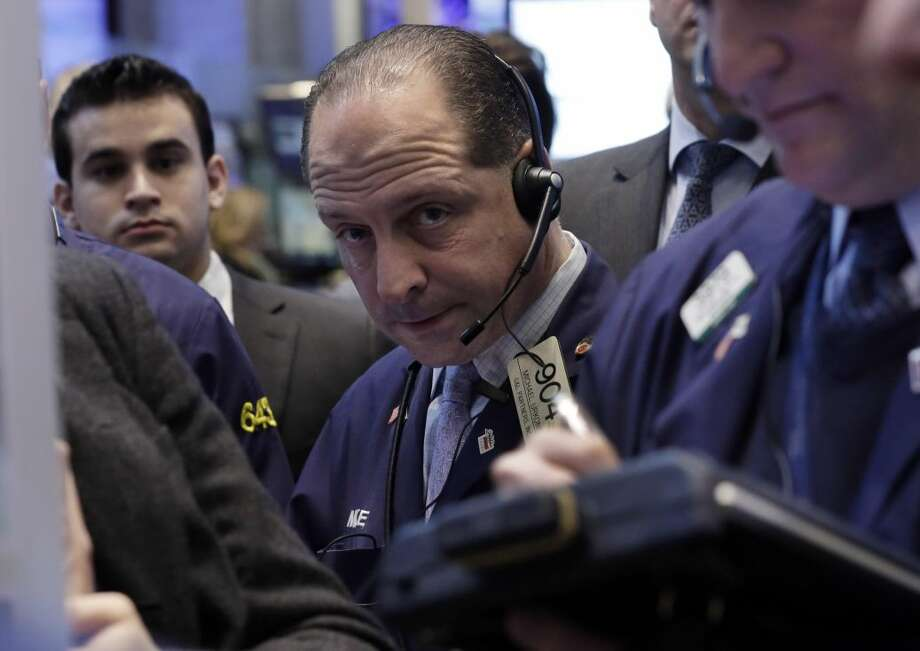 In this Friday, Jan. 25, 2013, photo, Trader Michael Urkonis, center, works on the floor of the New York Stock Exchange. Wall Street appeared headed for a day of trade without drama Monday Jan. 28, 2013. (AP Photo/Richard Drew)