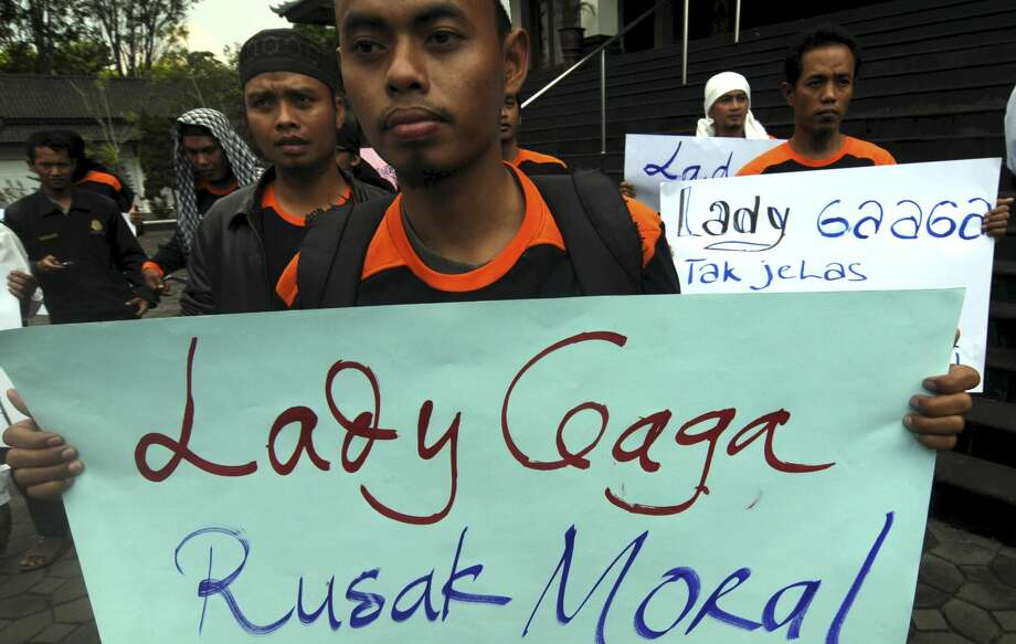 "Muslim youths hold posters during a protest against Lady Gaga's concert that is scheduled to be held on June 3, in Solo, Central Java, Indonesia, on Wednesday. Lady Gaga might have to cancel her sold-out show in Indonesia because police worry her sexy clothes and dance moves undermine Islamic values and will corrupt the country's youth. The writing on the poster says ""Lady Gaga corrupts moral."" (AP Photo)"