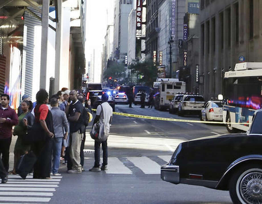 Pedestrians stand near Seventh Ave. and 32nd street as police officers work a crime scene Thursday, Sept. 15, 2016, in New York. (AP Photo/Frank Franklin II)