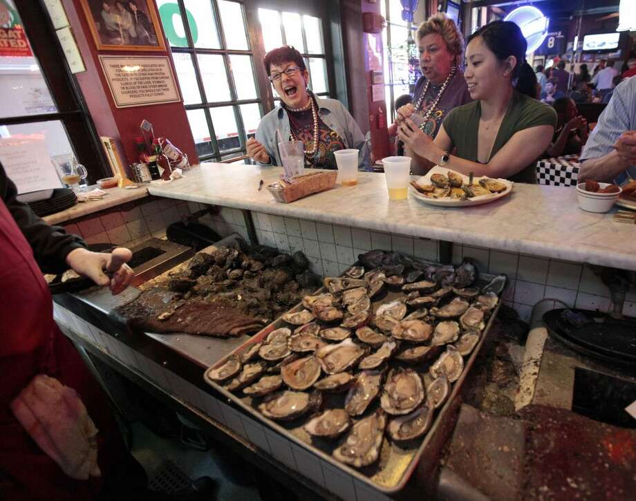 "In this May 4, 2011 file photo, raw oysters are served to customers at the oyster bar inside the Acme Oyster House in New Orleans. Tradition will hold for Cajun chef John Folse this Thanksgiving. ""I'm confident enough that I've got a big ol' pot of oyster dressing going right now,"" Folse said, when asked about the availability of Gulf of Mexico oysters more than two years after the BP oil spill, and months after Hurricane Isaac raked the Louisiana coast. (AP Photo/Gerald Herbert, File)"