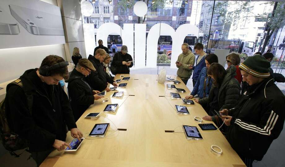 In this Friday, Nov. 2, 2012 file photo, Shoppers check out the new Apple iPad mini at the Apple store on Michigan Ave. in Chicago. Apple said Monday, Nov. 5, 2012, it sold 3 million iPads of all kinds in the first three days it sold the new Mini model. (AP Photo/M. Spencer Green, FIle)