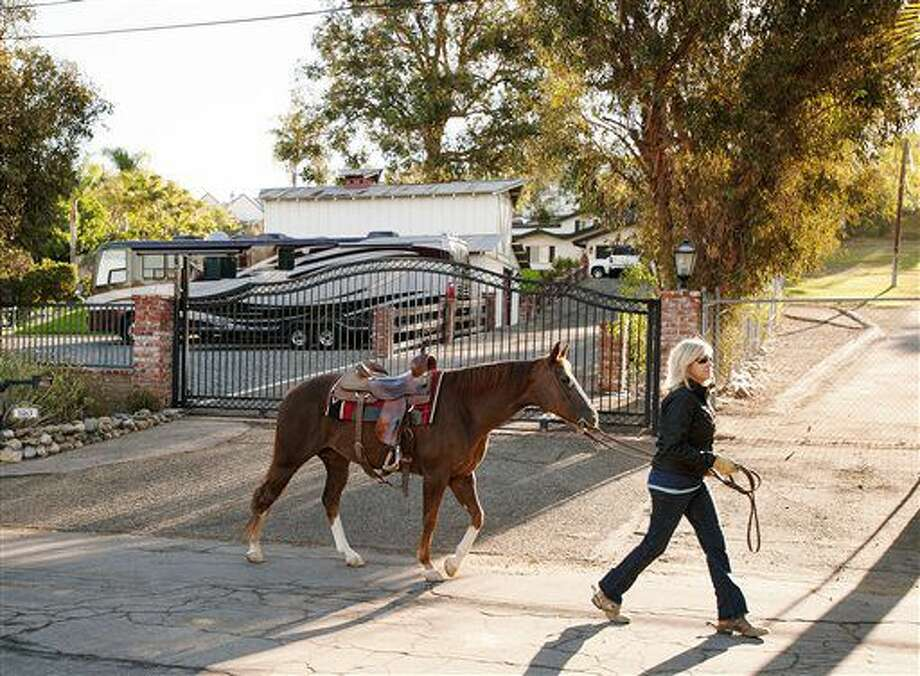Neighbor Jill Dombroske walks her horse Lola outside the home of Robert Gordon and his wife, Sharon Gordon in Orange, Calif., Thursday, Sept. 15, 2016. Police said they were found dead Wednesday and a neighbor said they were the father and stepmother of former NASCAR racer Robby Gordon. (Ken Steinhardt/The Orange County Register via AP)
