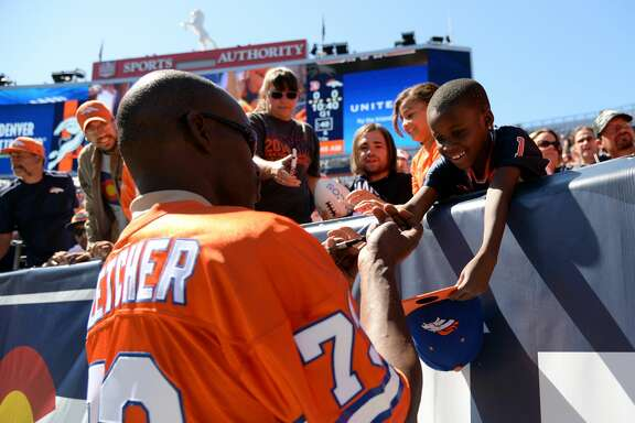 DENVER, CO - AUGUST 02: Former Denver Broncos Simon Fletcher, front, signs autographs to the fans during the Broncos scrimmage at Sports Authority Field at Mile High. Denver, Colorado. August 02. 2014. (Photo by Hyoung Chang/The Denver Post via Getty Images)
