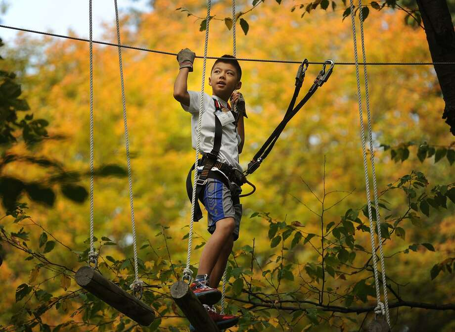 Ryan Huang, 12, of the Southport section of Fairfield, takes on a blue level aerial ropes course with confidence at the Adventure Park at the Discovery Museum in Bridgeport on Sunday. Photo: Brian A. Pounds / Hearst Connecticut Media / Connecticut Post