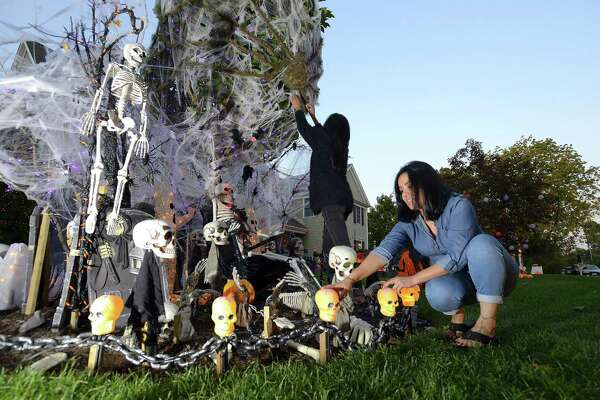 Lucia Moran and Ruth Diaz adjust Halloween decorations  on Tuesday, Oct. 18 2016 at the home of Karen Cingari who Moran and Diaz helped set up the massive Halloween display in front of her Stamford home for the holiday.