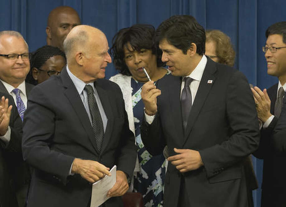 Senate President Pro Tem Kevin de Leon, D-Los Angeles, right, thanks Gov. Jerry Brown after he gave de Leon the pen used to sign legislation that will automatically enroll millions of private-sector workers in retirement saving accounts, at the Capitol Thursday, Sept. 29, 2016, in Sacramento, Calif. De Leon's bill, SB-1234, creates a state-run retirement program for nearly 7 million who don't have an employer-sponsored plan. (AP Photo/Rich Pedroncelli)