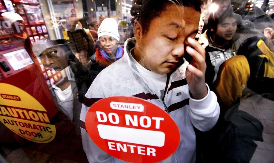 In this Friday, Nov. 28, 2008, file photo, Frankie Lee, the first in a line of several hundred shoppers at a Wal-Mart in Oakland, Calif., rubs his eyes shortly before the store opens at 5 a.m. (AP Photo/Noah Berger)