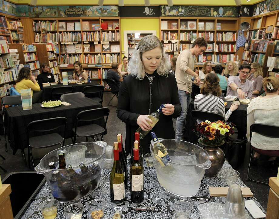 Coley Gold, events manager for Booksmith, serves drinks at one of the popular store's book swaps. Photo: Carlos Avila Gonzalez, The Chronicle