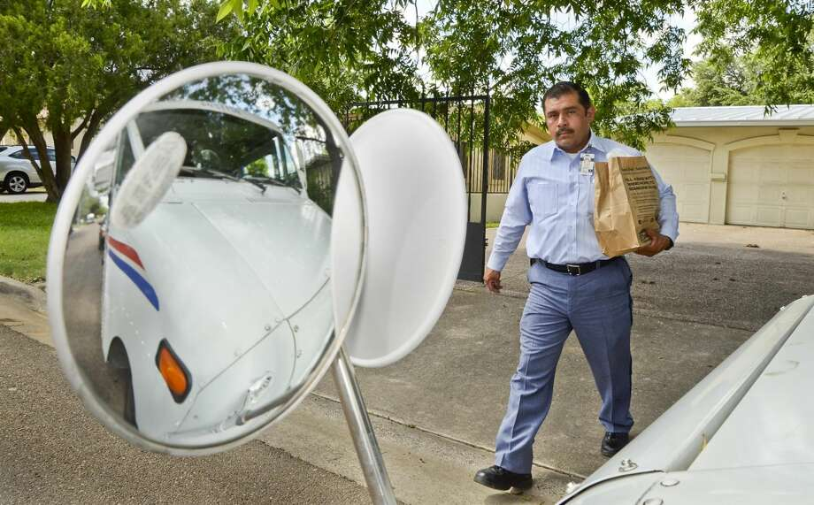 Anacleto De Luna, a mailman for the United States Postal Service, walks back to his vehicle with a bag of donated food left at the doorstep of a home on Galveston Street, Saturday afternoon. (Photo by: Danny Zaragoza/Laredo Morning Times)