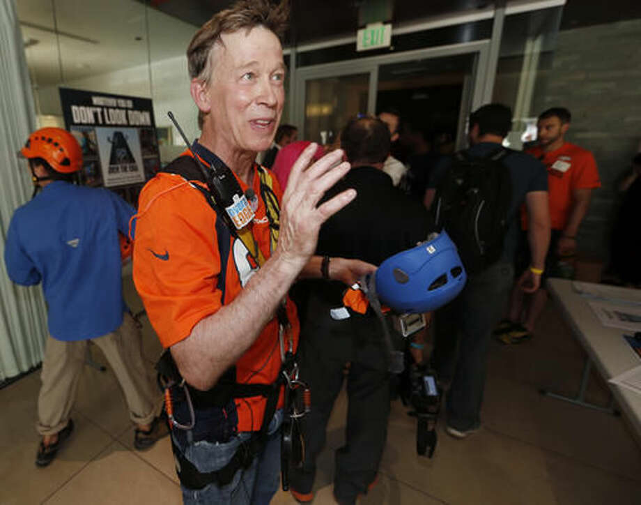 Colorado Gov. John Hickenlooper talks with reporters after rappelling down a downtown building as part of the Over The Edge fundraiser which benefits the Cancer League of Colorado, late Thursday, Sept. 8, 2016, in Denver. (AP Photo/David Zalubowski)