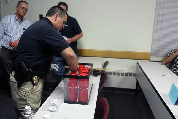 Det. Philip Restieri begins a super glue fuming technique to develop class members' fingerprints on plastic cups during the sixth class of the Citizens' Police Academy in Westport, Conn. on Oct. 13, 2016.