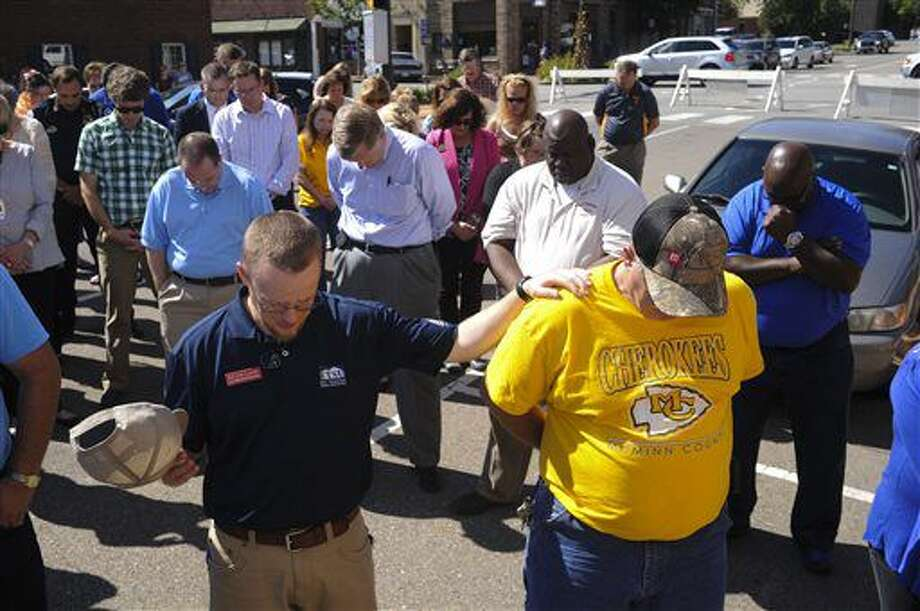 Kevin Lane, left, and Kenny Eaves take part in a vigil for the victims of the Thomas & Betts plant shooting, Friday, Sept. 23, 2016, in Athens, Tenn. Ricky Swafford who fatally shot two supervisors and then killed himself at an electrical components plant in eastern Tennessee had a state-issued permit to carry handguns in public, law enforcement officials said Friday. (Paul Efird/Knoxville News Sentinel via AP)