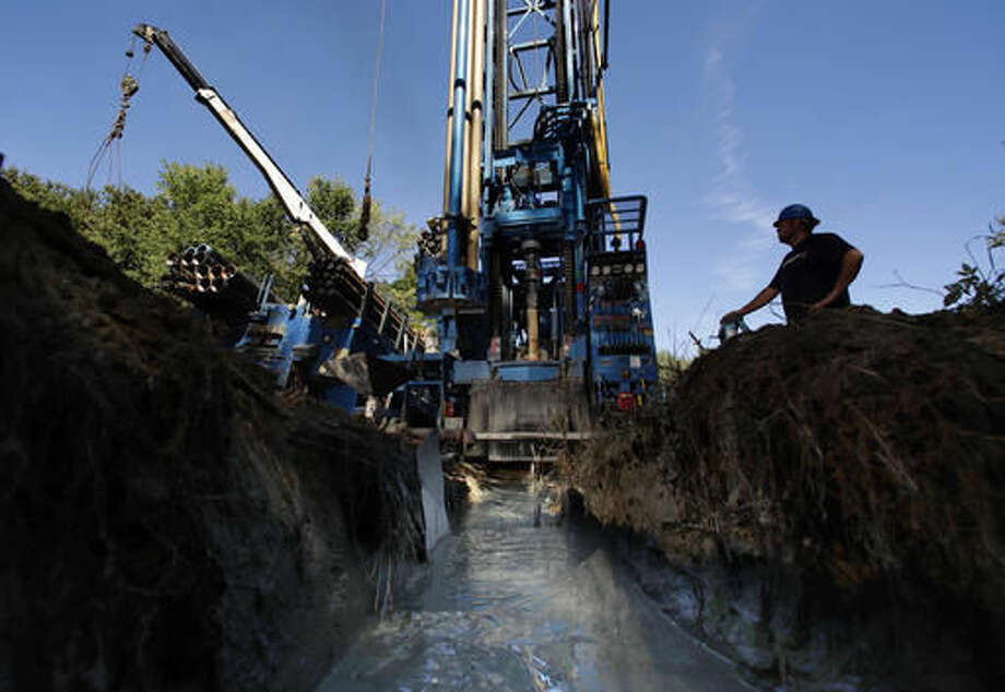Josh Matthews keeps watch of the machinery as a well is drilled at a home, Thursday, Sept. 22, 2016, in Hampton Falls, N.H. Many private wells have gone dry amid this summer's prolonged drought and dry weather in the Northeastern U.S.(AP Photo/Robert F. Bukaty)