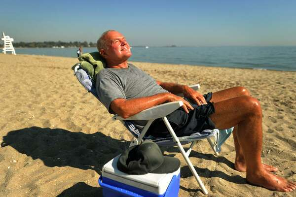 Above, Peter Paris, of Fairfield, enjoys the unseasonably warm weather and even considers taking a swim at Penfield Beach on Tuesday.