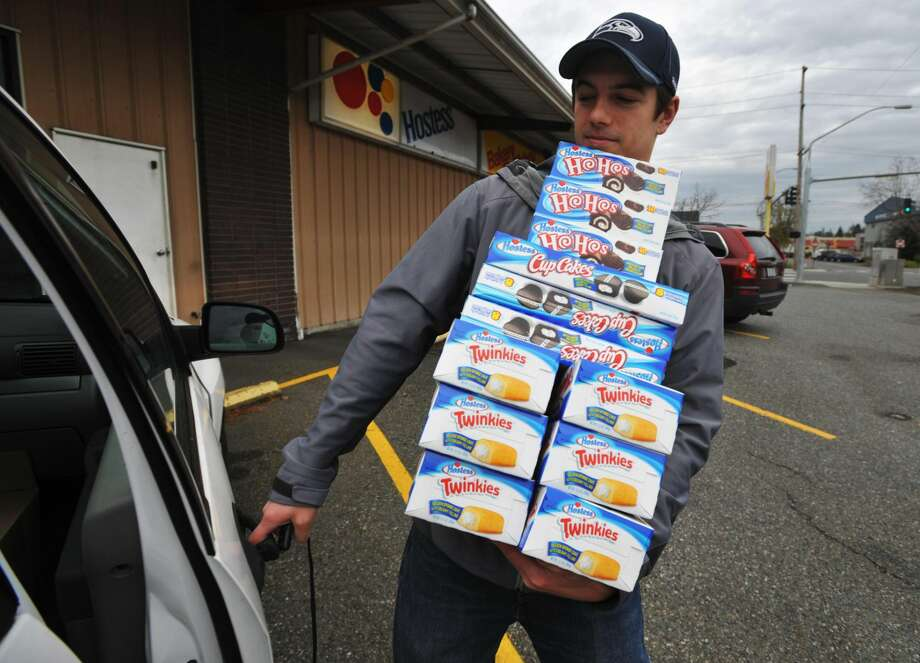 Andy Wagar loads Twinkies, Ho-Hos and Cup Cakes into a van outside the Wonder Bakery Thrift Shop in Bellingham, Wash., Friday, Nov. 16, 2012, after Hostess Brands Inc. said it would shutter is operations after years of struggling with management turmoil, rising labor costs and the ever-changing tastes of Americans even as its pantry of sugary cakes seemed suspended in time. (AP Photo/The Bellingham Herald, Philip A. Dwyer)