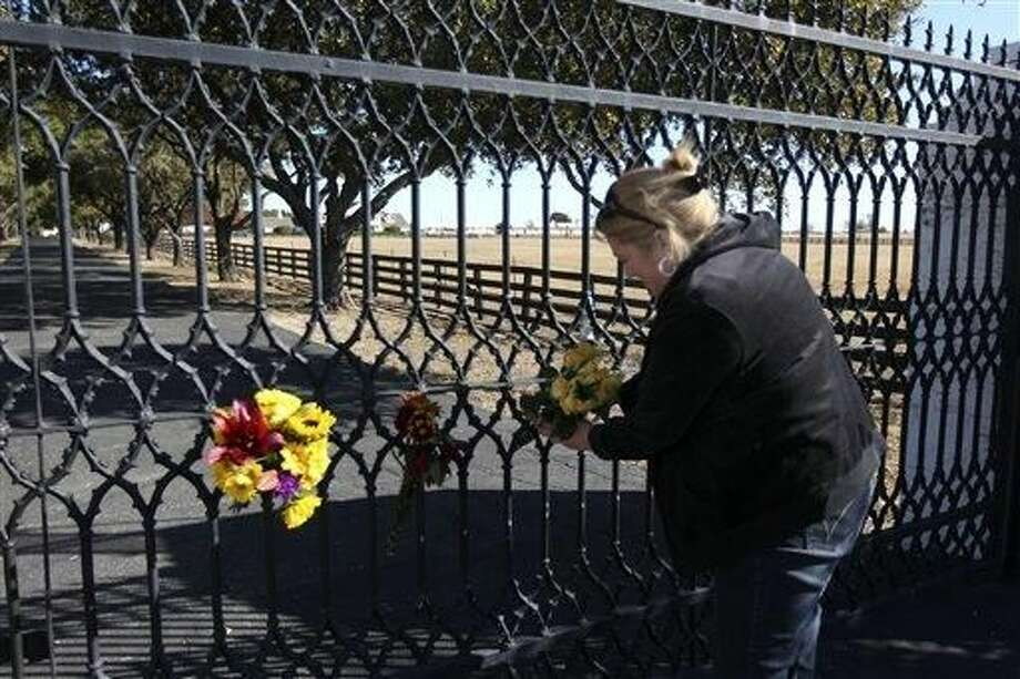"Kelli Pearson of Rowlett, attaches a bouquet of yellow roses to the front gate of Southfork Ranch, setting for TV show ""Dallas "", in Parker, Texas, in memory of actor Larry Hagman Saturday, Nov. 24 2012. Hagman, known as J. R. Ewing in the TV show, died Friday, Nov. 23, 2012 in Dallas. He was 81. (AP Photo/The Dallas Morning News, Ron Baselice)"