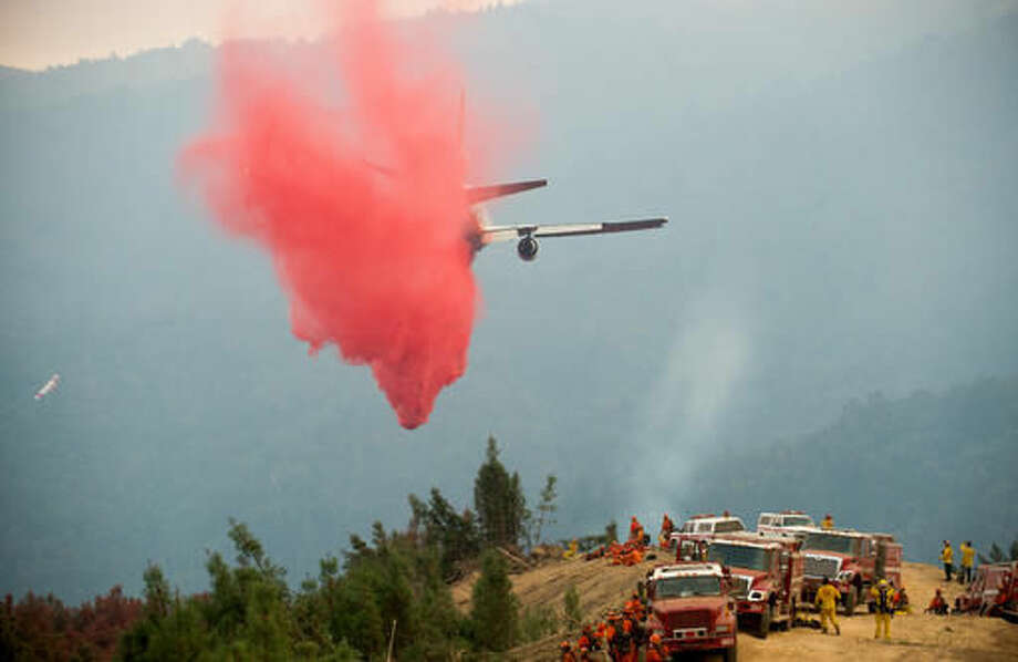 A VLAT (Very Large Air Tanker) drops retardant to create a fire break while battling a wildfire near Morgan Hill, Calif., Wednesday, Sept. 28, 2016. A growing and destructive wildfire moved toward remote California homes in the Santa Cruz Mountains on Wednesday as it scorched its way through bone-dry brush and trees. (AP Photo/Noah Berger)
