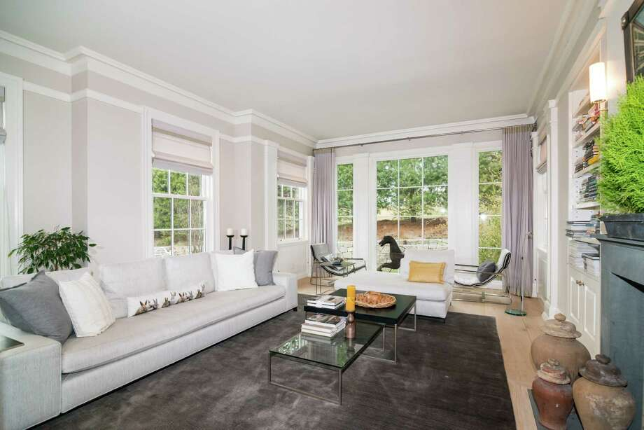 The formal living room has floor-to-ceiling windows, a fireplace and built-in bookshelves. Photo: Contributed Photo / Westport News