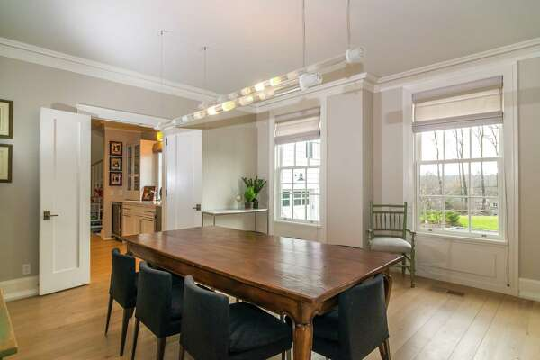 The formal dining room of this 7,659-square-foot custom colonial house provides access into the butler's pantry.