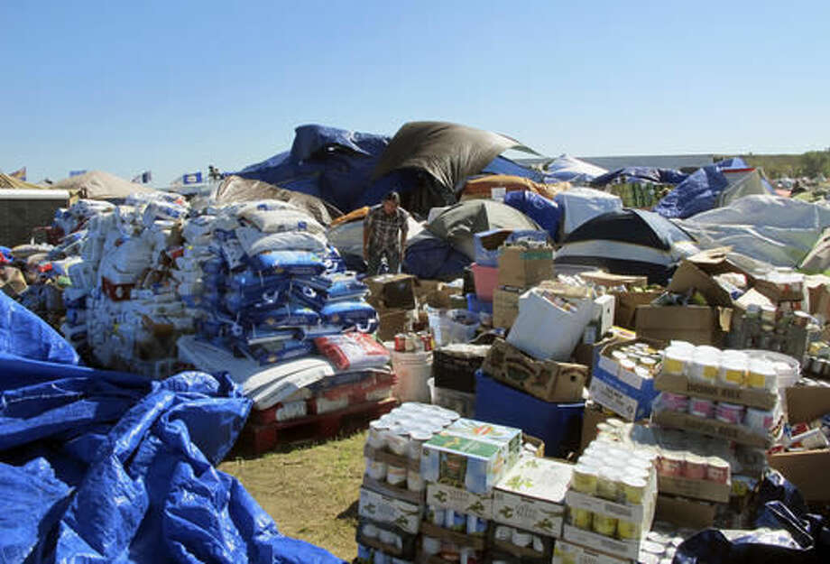 In this Wednesday, Sept. 14, 2016, photo, a volunteer sorts through donated food near the Standing Rock Sioux Reservation in North Dakota. Tribal officials say donated food and clothing has come from around the world to support those opposing the $3.8 billion Dakota Access pipeline. (AP Photo/ James MacPherson).