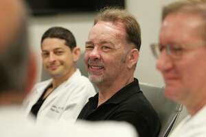 Dr. Jesse Selber, a plastic surgeon with MD Anderson (left-right), James Boysen, and Dr. Michael Klebuc, a plastic surgeon from Houston Methodist share a moment with Dr. Osama Gaber, director of Methodist's transplant program as they talk about the success they had with Boysen's scalp transplant. Boysen celebrated his one-year anniversary as a transplant patient in May.