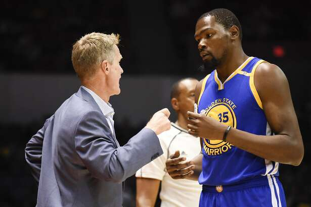 Head coach Steve Kerr talks with Golden State Warriors forward Kevin Durant (35) during an NBA preseason basketball game against the Los Angeles Lakers Wednesday, Oct. 19, 2016, in San Diego. (AP Photo/Denis Poroy)