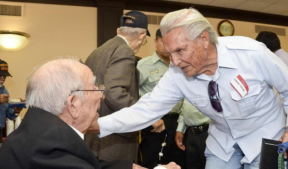 World War II veteran Jose Perez meets with fellow veteran, Edmundo Durante, Friday afternoon after a ceremony honoring several World War II veterans at the Justice Center's County Court Room No. 2. (Photo by Danny Zaragoza/Laredo Morning Times)