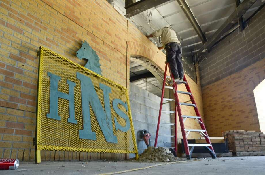 A welded sign with the Nixon High School initials lays against a wall as a construction worker stands on a ladder chipping away at the wall of the administrative building Wednesday afternoon at the Nixon High School campus. (Photo by Danny Zargoza/Laredo Morning Times)