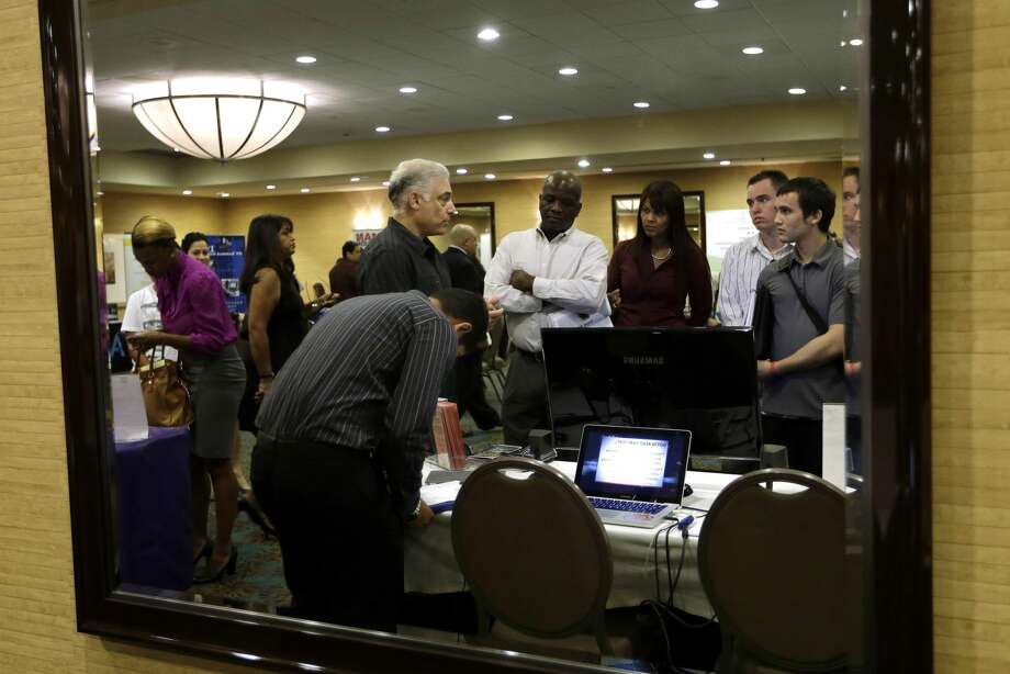In this Monday, Sept 17, 2012, file photo, Robert Orkin of the company TxT-Alert, third from left, talks with job seekers during a job fair held by National Career Fairs in Fort Lauderdale, Fla. The U.S. unemployment rate fell to 7.8 percent last month, dropping below 8 percent for the first time in nearly four years. (AP Photo/Lynne Sladky, File)