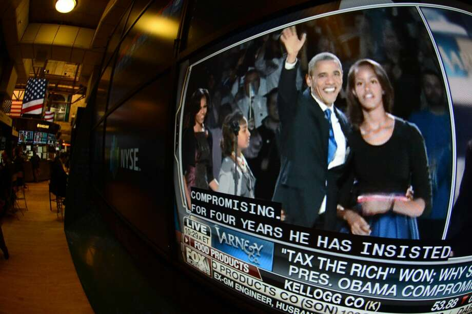 """A television feed on the floor of the New York Stock Exchange shows Pres. Barack Obama, left, and his daughter, Malia, the day after he was re-elected, Wednesday, Nov. 7, 2012 in New York. With President Barack Obama elected to another term, U.S. investors dumped stocks Wednesday and turned their focus to a world of problems, including a """"fiscal cliff"""" of tax increases and spending cuts at home and a deepening recession in Europe. (AP Photo/Henny Ray Abrams)"""