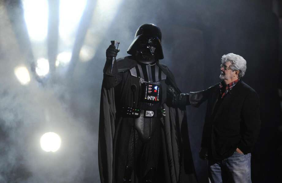 "In this Oct. 15, 2011 file photo, ""Darth Vader"" accepts the Ultimate Villain award from ""Star Wars"" creator George Lucas during the 2011 Scream Awards, in Los Angeles. (AP Photo/Chris Pizzello, File)"
