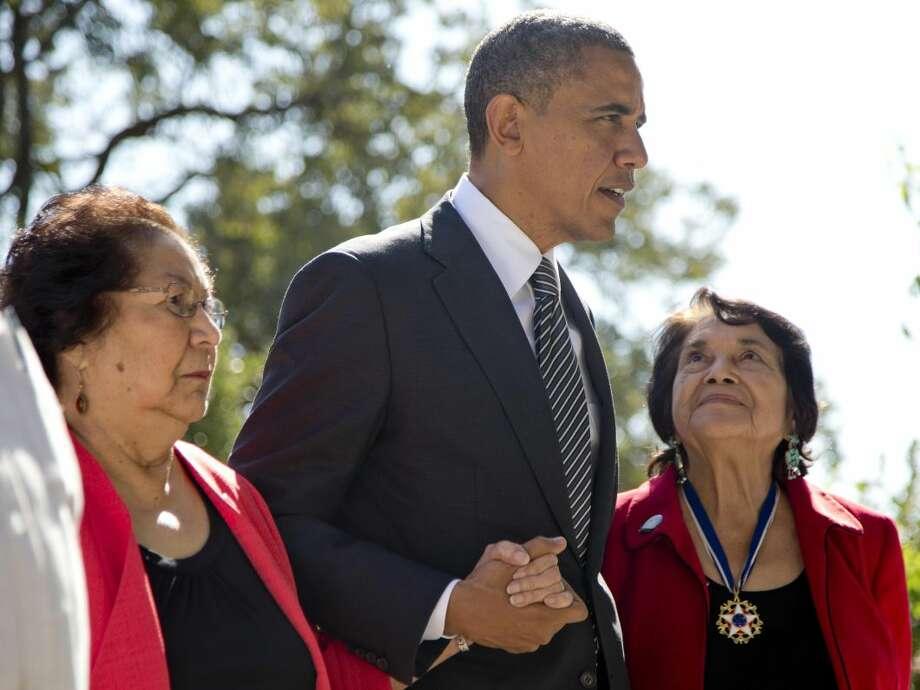 El presidente Barack Obama camina con la viuda del dirigente campesino César Chávez, Helen F. Chávez, a la izquierda, y con Dolores Huerta, Cofundadora del sindicato de trabajadores agrarios. El mandatario estadounidense designó la casa y tumba del sindicalista como monumento nacional. (Foro por Carolyn Kaster