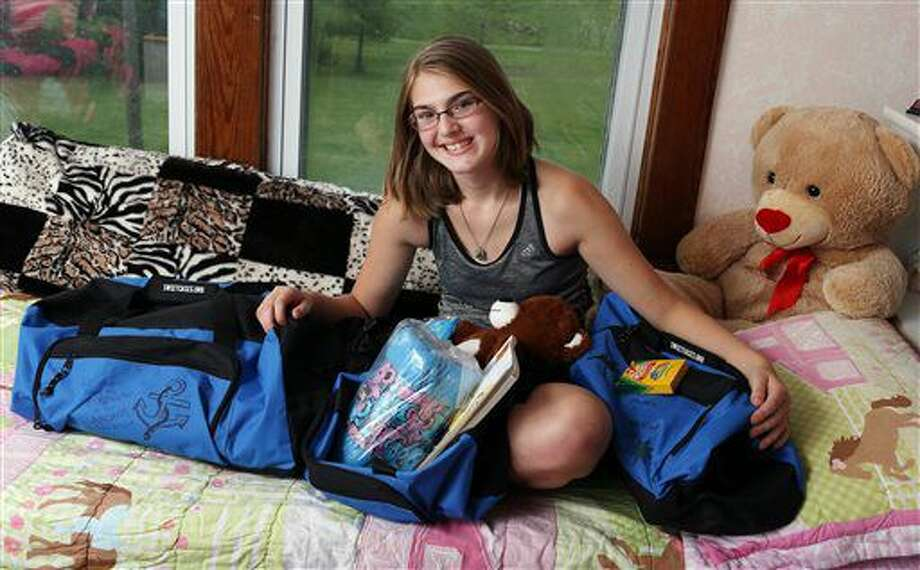 ADVANCE FOR WEEKEND EDITIONS SEPT 10-11 - In this Wednesday Aug. 24, 2016 photo, Sara Roth, 14, the adopted foster daughter of Les and Lora Roth, displays filled and decorated bags meant for distribution to foster children when they go to a foster home in her rural Donnellson, Iowa, home. (John Lovretta/The Hawk Eye via AP)